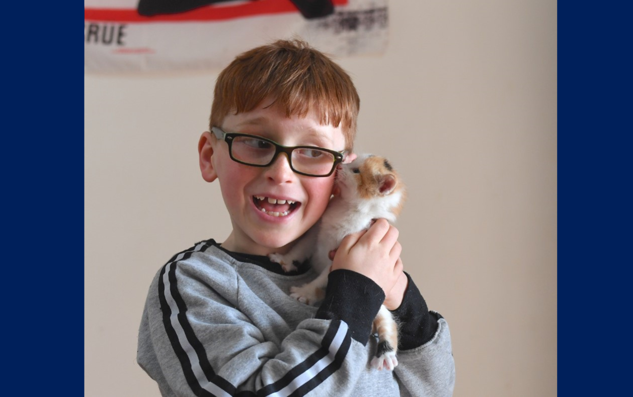 zavier joyfully holding a kitten