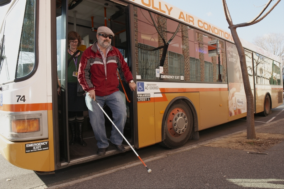 Person with long cane disembarking from a bus