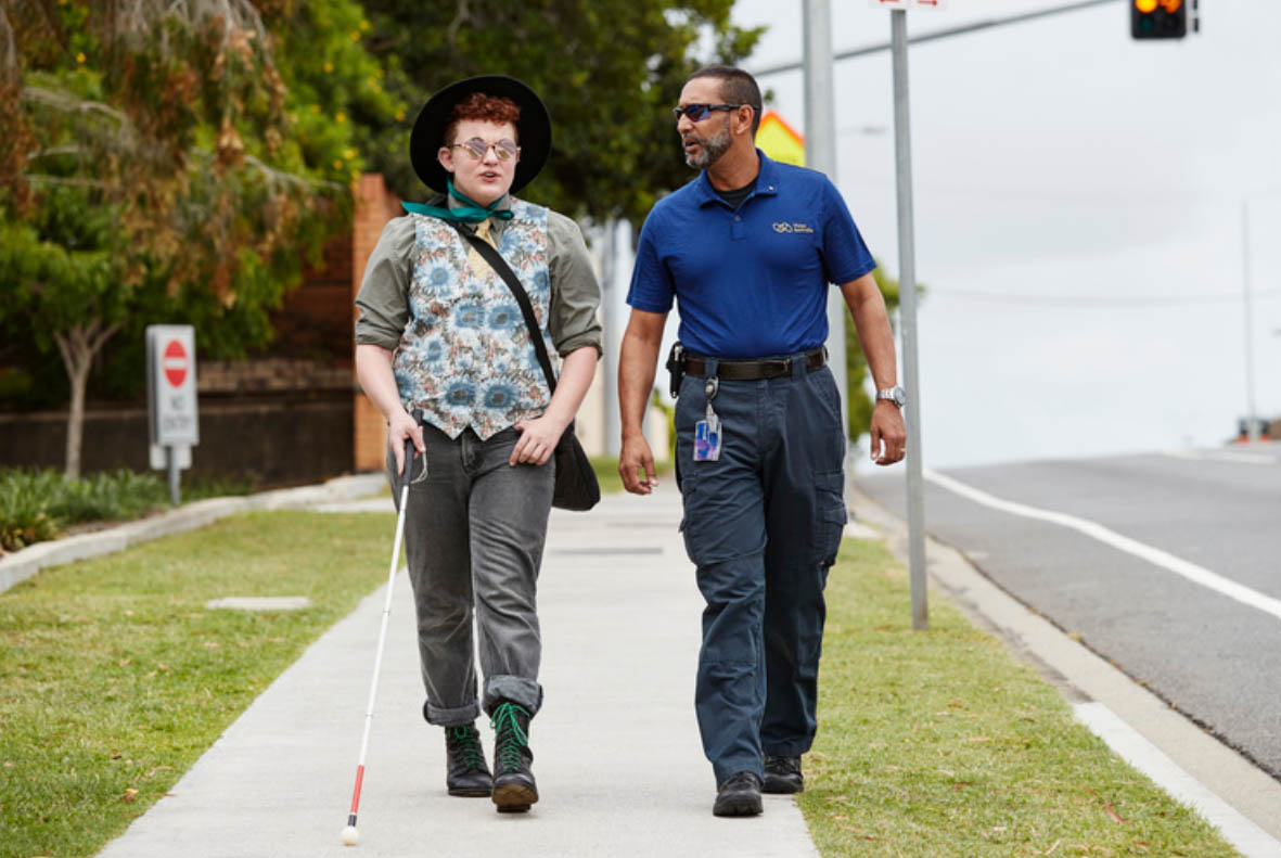 A young man walking with his white cane, walking alongside a staff from Vision Australia.