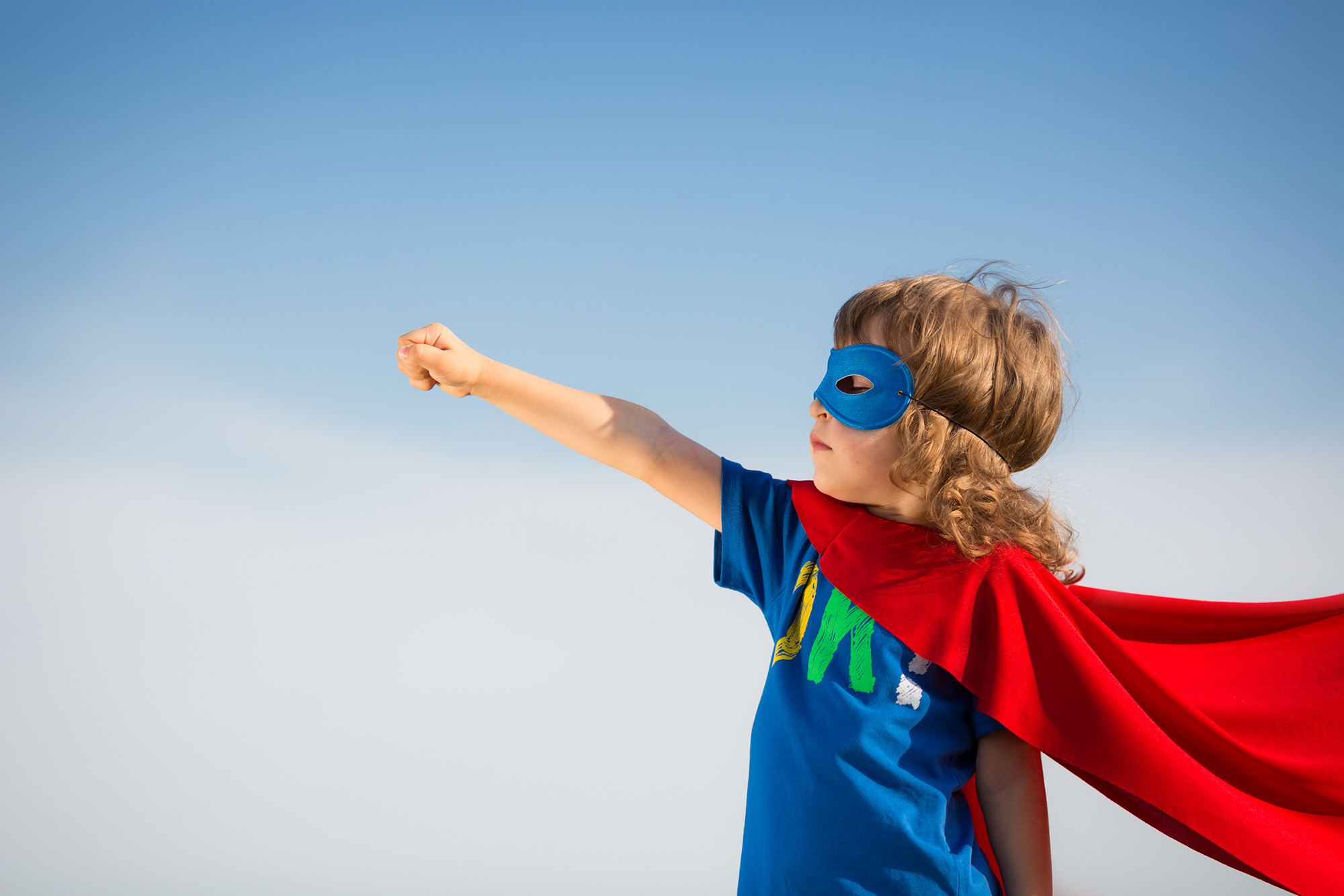 Small child with mask and cape, arm is stretched upwards and hand in a fist